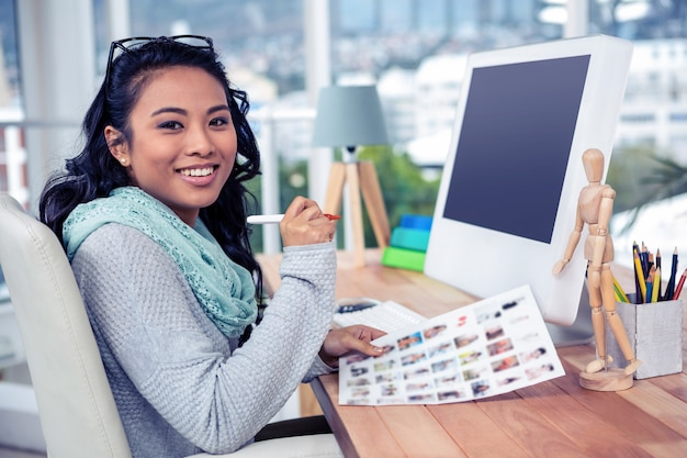 Asian businesswoman holding paper sheet in office
