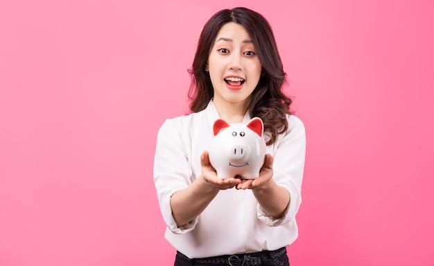 Asian businesswoman holding piggy in her hand, saving money concept