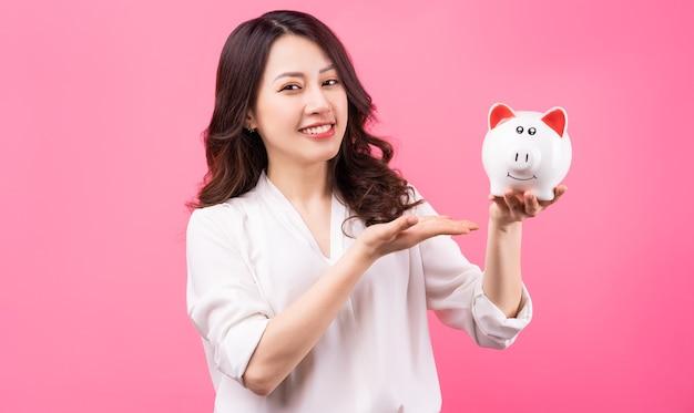 아시아 사업가 그녀의 손에 돼지를 들고 돈 개념을 절약