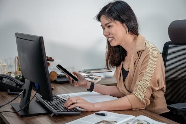 顧客サービスの概念のためのオフィス、ビジネスおよびプロジェクト計画でコンピューターとモバイルでの作業とフォーマルなスーツでアジア女性実業家