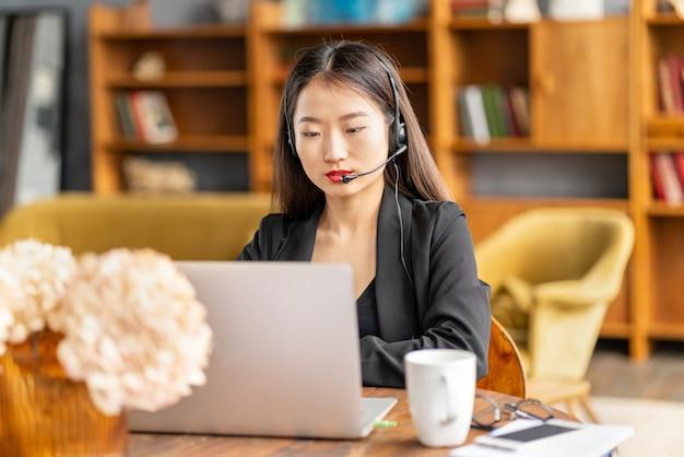 사무실에서 노트북에 전화 회의 및 화상 채팅으로 말하는 헤드셋에서 아시아 사업가