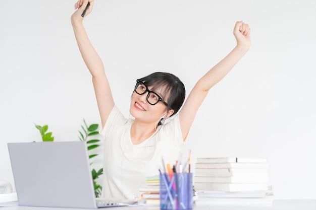 Азиатская бизнес-леди потягивает плечи после окончания работы