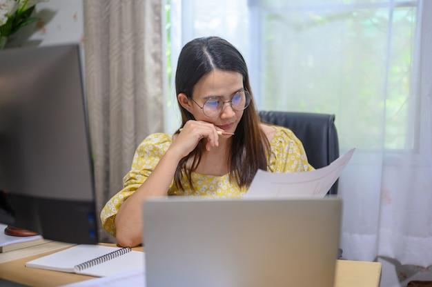 自宅でオンラインで働くアジアの実業家。居間のタイの女性のライフスタイル。社会的距離と新しい正常。