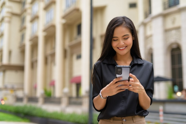 Asian businesswoman outdoors in city street using mobile phone while smiling and texting
