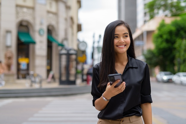 Asian businesswoman outdoors in city street using mobile phone while walking and smiling