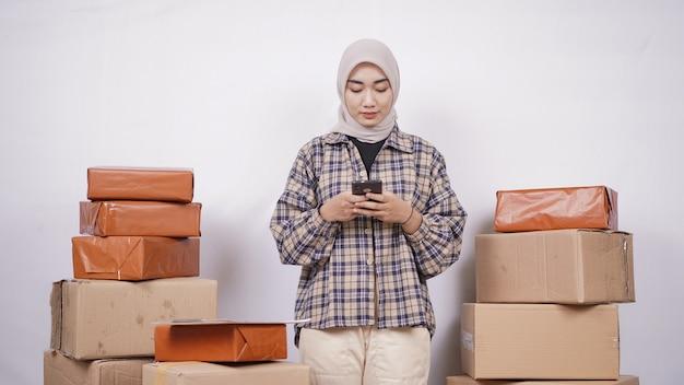 白い背景で隔離の彼女のスマートフォンで遊ぶアジアの実業家