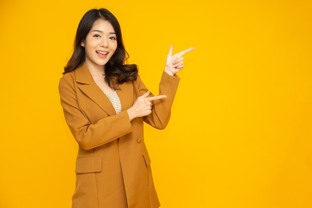 Asian businesswoman pointing to empty copy space isolated on yellow background