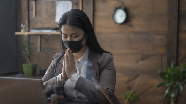 Asian businesswoman prays in office putting her palms together with closed eyes while sitting at table, pandemic concept