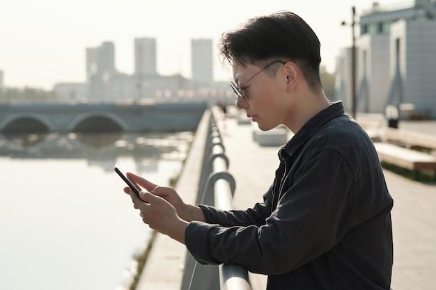 강변에서 스마트폰으로 스크롤하는 아시아 사업가