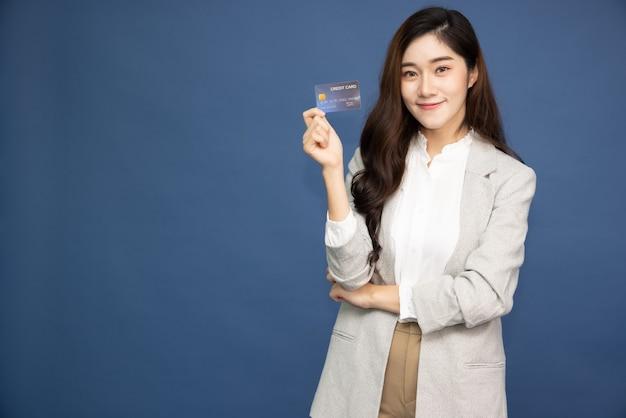 파란색 배경에 고립 된 신용 카드를 보여주는 아시아 사업가