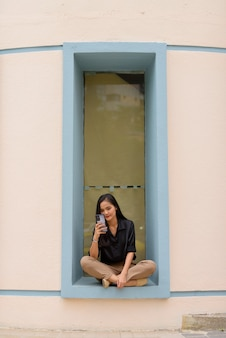 Asian businesswoman sitting and relaxing while using mobile phone in city