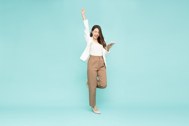 Asian businesswoman standing and hands up and holding calculator isolated on green background