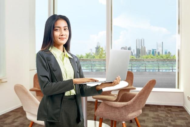 自宅で仕事のラップトップを使用しながら立っているアジア女性実業家