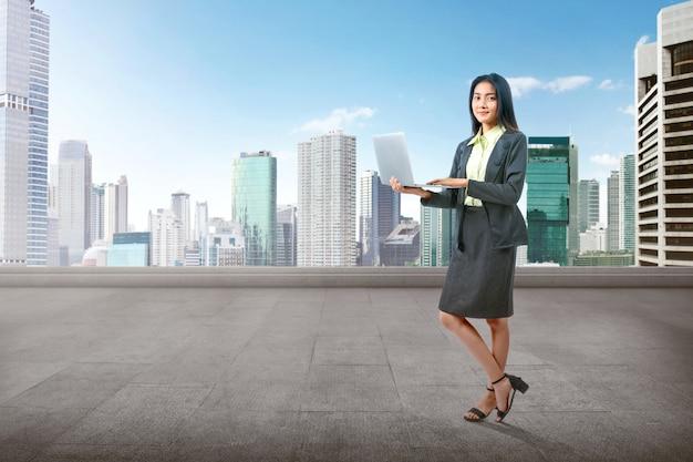 ラップトップを使用しながら立っているアジア女性実業家