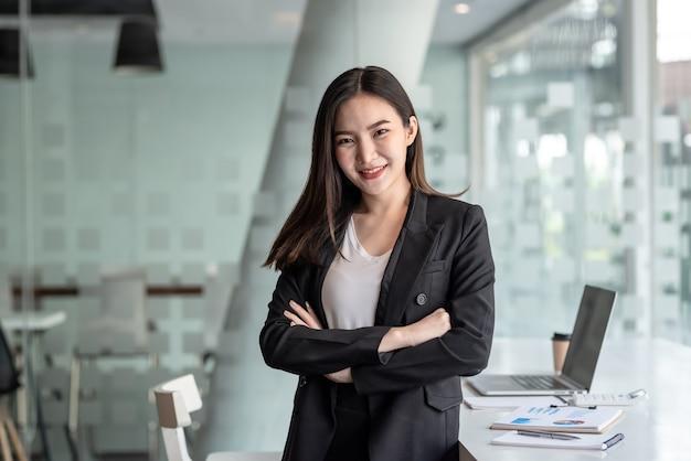 オフィスでカメラを見ている腕を持って立っているアジアの実業家。
