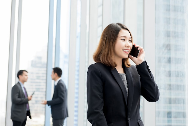 Asian businesswoman talking on cell phone in office building hallway