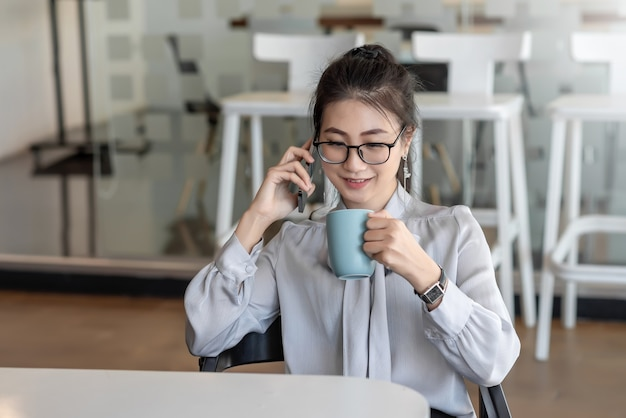 Азиатская деловая женщина разговаривает по мобильному телефону и пьет кофе в офисе
