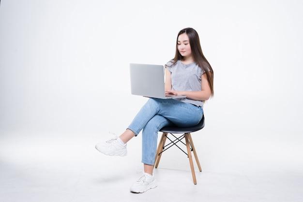 아시아 사업가 전화로 얘기 하 고 자에 앉아있는 동안 노트북을 찾고. 일하는 여성이 자신있게 다리를 꼬고 앉았다.