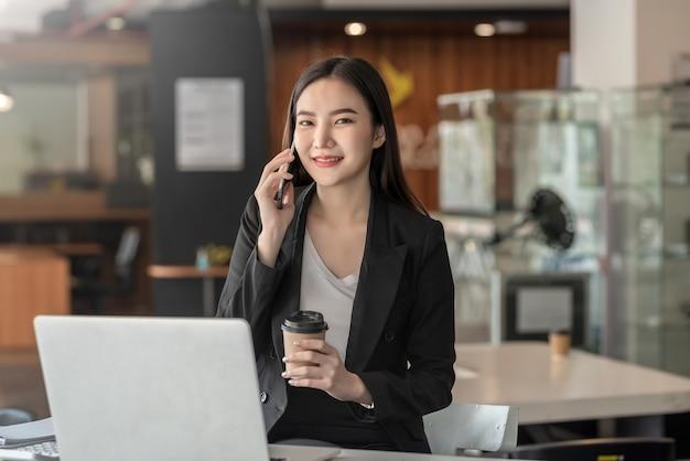 Азиатский бизнесмен разговаривает по телефону, держа кружку кофе в офисе.