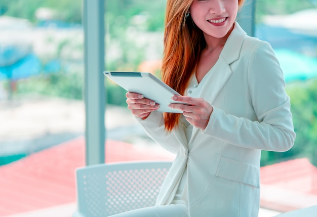 Asian businesswoman using a digital tablet standing in front of windows in city building.