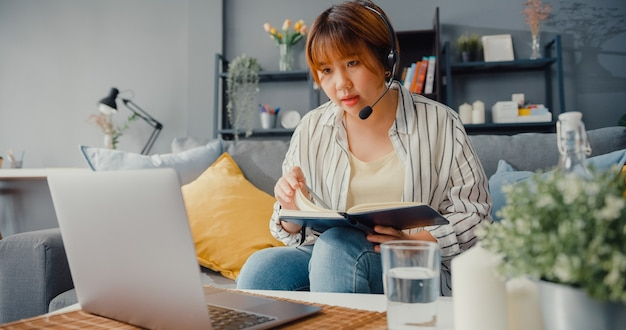 Asian businesswoman using laptop talk to colleagues about plan in video call while working from house at living room