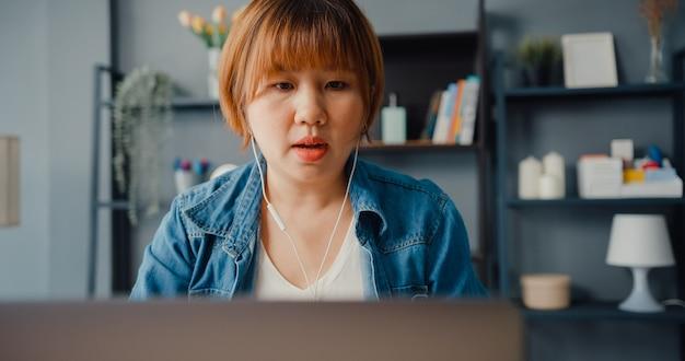 ノートパソコンを使用しているアジアの実業家は、居間で家から働いている間、ビデオ通話の計画について同僚に話します