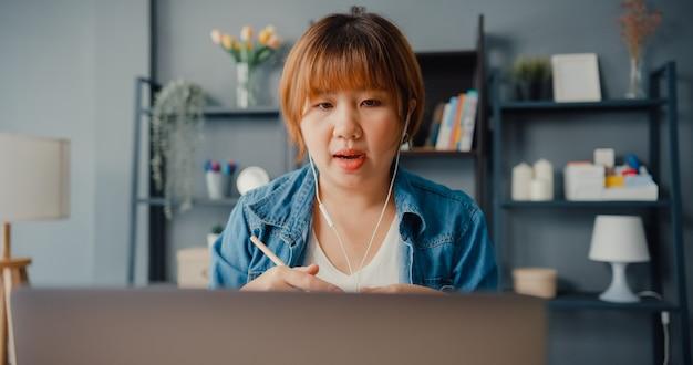 ノートパソコンを使用しているアジアの実業家は、居間で家から働いている間、ビデオ通話の計画について同僚に話します Premium写真