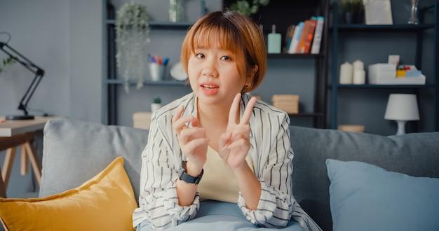 거실에서 집에서 작업하는 동안 화상 통화 계획에 대해 동료에게 노트북 이야기를 사용하는 아시아 사업가