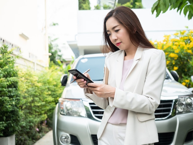 Asian businesswoman using smart phone against a car.