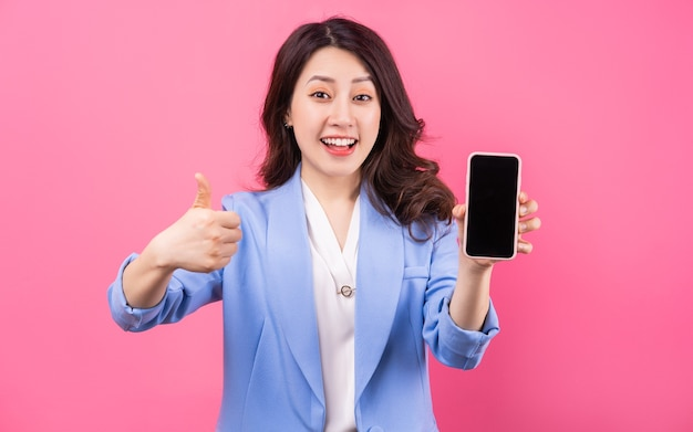 Asian businesswoman using smartphone on pink