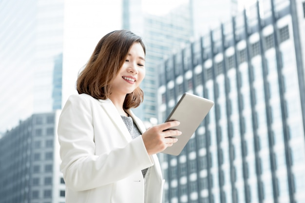 Asian businesswoman using tablet computer outdoors on blur office building