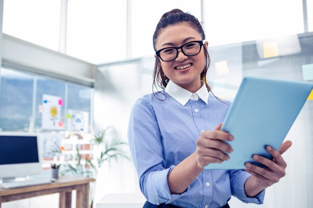 Asian businesswoman using tablet in office