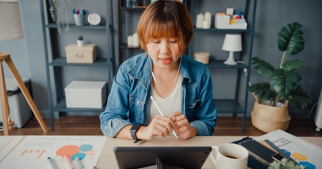 タブレットを使用しているアジアの実業家は、居間で家から働いている間、ビデオ通話の計画について同僚に話します