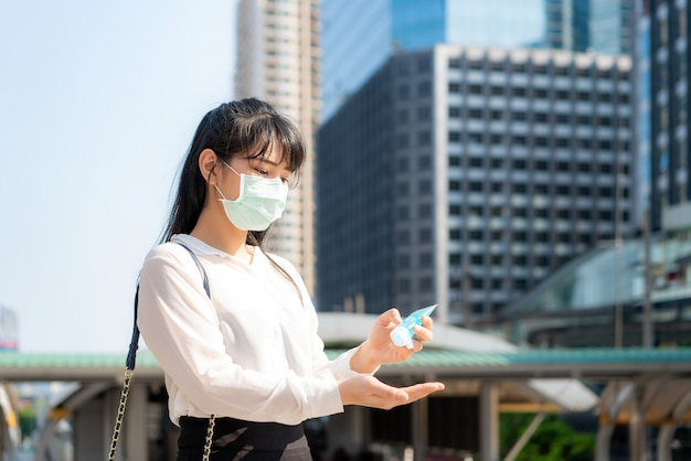Asian businesswoman using wash hand sanitizer gel dispenser while coronavirus network outbreak, health care and cleaning for prevent covid19 conceptin bangkok city downtown, thailand.