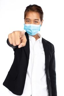 アジアの女性実業家は、フォーマルな黒いスーツのジャケットで手術用フェイスマスクを着用し、カメラに人差し指、カメラを見て、白い背景で隔離、彼女の手に焦点を当てる、covid-19コンセプト