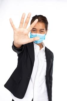 アジアの女性実業家は、フォーマルな黒のスーツジャケットに手術用フェイスマスクを着用し、5本の指を見せ、ジェスチャーを停止し、カメラを見て、白い背景で隔離のスタジオライト、コロナウイルス、covid19コンセプト