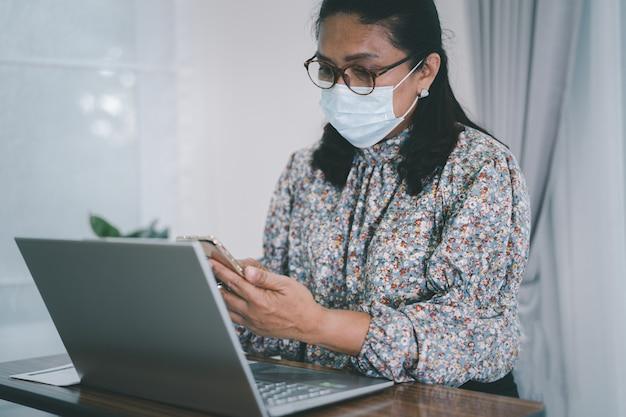 自宅で仕事をするためにコロナウイルスを保護するためのマスクを身に着けているアジアの実業家