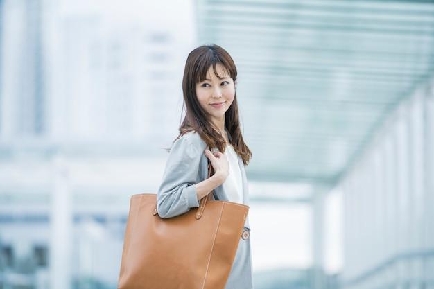 革のバッグを持つアジアの実業家