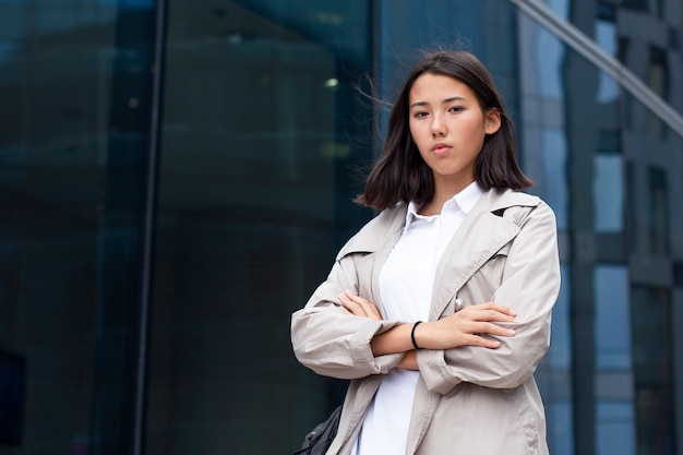 Asian businesswoman with hands crossed stand outside office modern glass building
