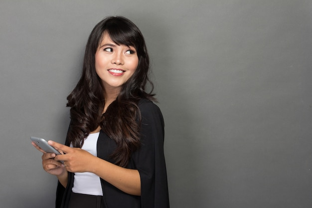 Asian businesswoman with her phone looking up