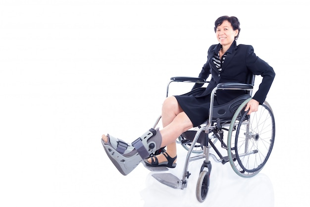 Asian businesswoman with leg brace sitting on wheelchair and smile over white background