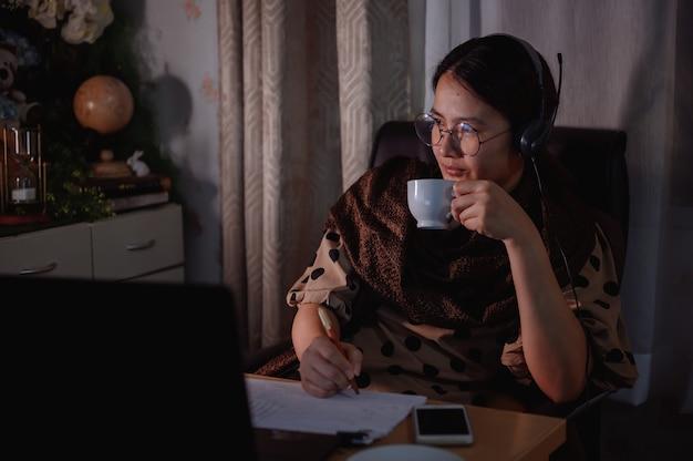 아시아 여성 사업가는 밤에 재택근무를 합니다. 일하는 여성의 라이프 스타일. 동료와의 온라인 커뮤니케이션 및 화상 회의. 사회적 거리두기와 뉴노멀.