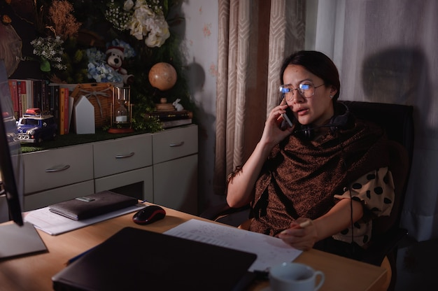 アジアの実業家は夜に残業します。働く女性のライフスタイル。同僚とのオンラインコミュニケーションとビデオ会議。社会的距離と新しい正常。
