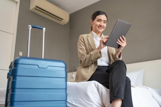 出張でホテルの部屋でタブレットを使用して作業しているアジアの実業家。出張の概念。