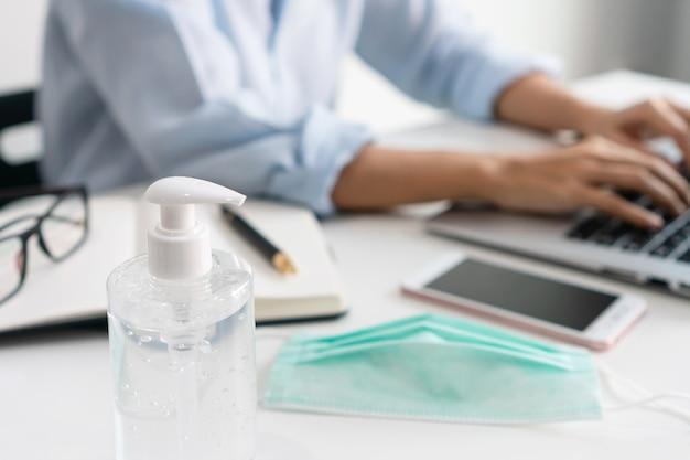 コロナウイルスの危機の間、テーブルの上に医療用マスクと手指消毒剤を持って職場で働いているアジアの実業家。在宅勤務、ビジネス、ヘルスケア、新しい通常のライフスタイルのコンセプト。閉じる