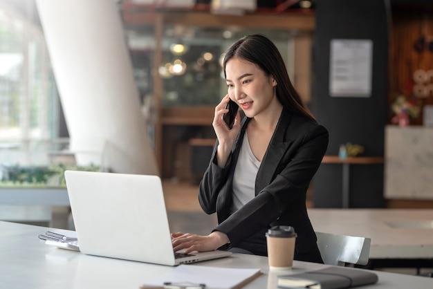 Азиатский бизнесмен, работающий на ноутбуке, разговаривает по телефону с клиентами в офисе.