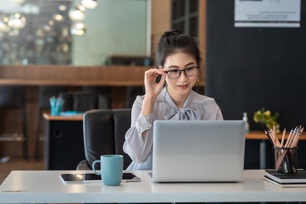 Азиатская деловая женщина, работающая на ноутбуке на своем столе в офисе.