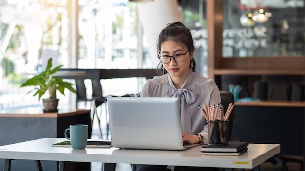 Азиатский бизнесмен работает на ноутбуке в офисе.