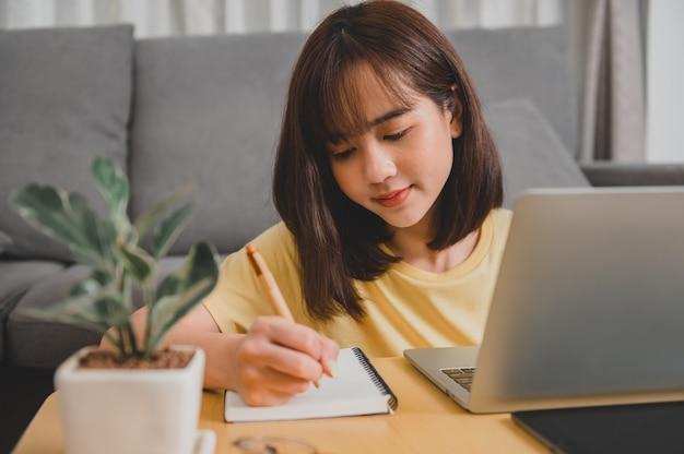 自宅で一人でオンラインで働くアジアの実業家。居間の女性のライフスタイル。社会的距離とニューノーマル。