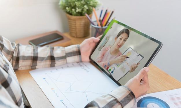 Donna d'affari asiatica che lavora in remoto da casa e webinar per riunioni di videoconferenza virtuale con colleghi uomini d'affari. distanza sociale a casa concetto di ufficio.